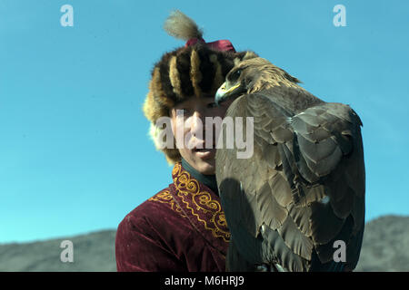A Kazakh eagle hunter with his golden eagle at the 2017 golden eagle festival, Olgii, western Mongolia. - Stock Image
