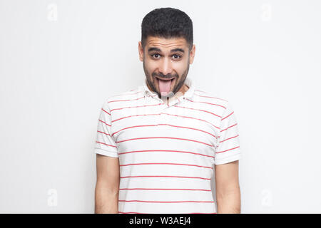 Portrait of funny crazy handsome bearded young man in striped t-shirt standing, tongue out and looking at camera with funny face. indoor studio shot, - Stock Image