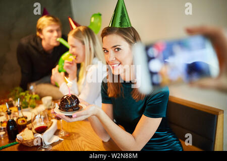 Foodblogger takes pictures of a piece of cake at a birthday party - Stock Image