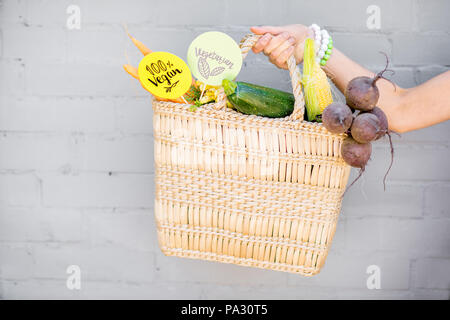 Holding straw bag full of fresh vegetables and green stickers with healthy food slogans on the gray wall background - Stock Image