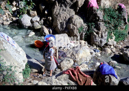 Moroccan women washing clothes on rocks in a stream close to Chefchauen, Rif mountains, Morocco, North Africa - Stock Image