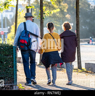 Strasbourg, Alsace, France, rear view of a man and 2 women walking on pavement, - Stock Image