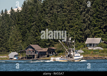 A fishing boat heads down the Wrangell Narrows past the tiny village of Petersburg on Mitkof Island in Frederick Sound with the Alaska Coast Range of mountains behind on Mitkof Island, Alaska. Petersburg settled by Norwegian immigrant Peter Buschmann is known as Little Norway due to the high percentage of people of Scandinavian origin. - Stock Image