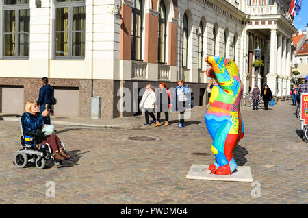 Woman in a wheelchair in the pedestrian city centre of Riga, Latvia - Stock Image