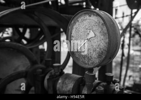 Rusty old pressure gauge in black and white. - Stock Image