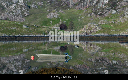 Boat with Blue Engine and orange buoy on Scottish Loch with refelections - Stock Image