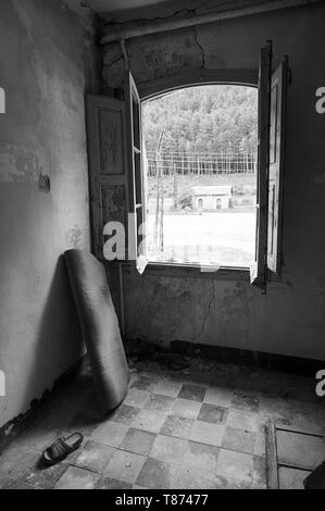 Interior of a room in the ruined facilities at the abandoned Canfranc International railway station (Canfranc, Pyrenees, Huesca,Aragon,Spain) B&W vers - Stock Image