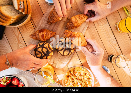 Group of friends family people viewed from vertical top view taking croissant and mixed food for breakfast morning activity - wooden table in backgrou - Stock Image