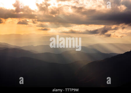 Scenic view of mountains against cloudy sky - Stock Image