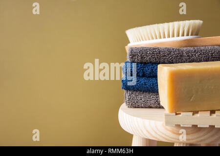 Hand crafted artisan olive oil soap body brush folded cotton towels stacked on wooden chair painted beige wall background. Spa wellness skin care orga - Stock Image
