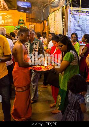 Hindu Priest with Worshiper Performing Ritual of Touching the Lamp, Sree Veera Hanuman Hindu Temple, Kuala Lumpur, Malaysia. - Stock Image