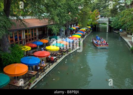 San Antonio River Walk riverwalk row of blue yellow orange umbrellas of outdoor cafes line river bank - Stock Image