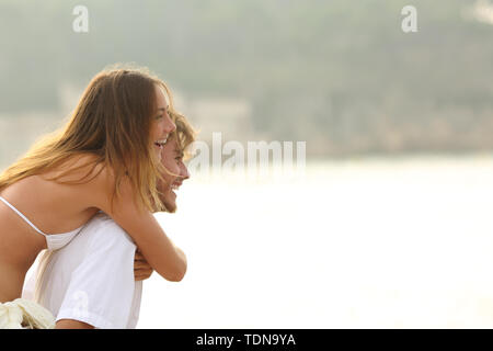 Funny couple joking on the beach with copy space on summer vacation - Stock Image
