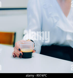 Selective focus view of corporate woman holding a plastic coffee cup. - Stock Image