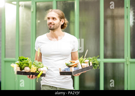 Portrait of a handsome man with boxes full of fresh raw vegetables standing outdoors on the green wall background - Stock Image