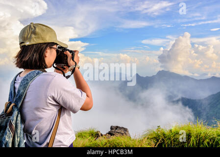 Hiker asian teens girl with digital camera and backpack taking photo beautiful natural of sierra sky clouds and - Stock Image