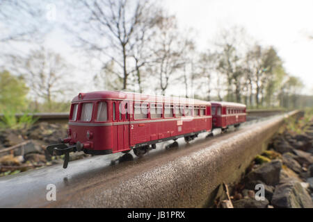 Red train model, bus-style train,  on real rails, original train served as local public transport, Celle, Germany - Stock Image