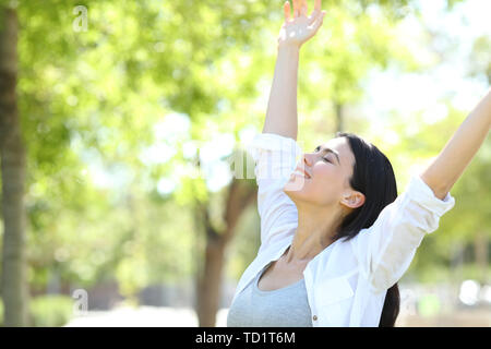 Happy adult woman celebrating new day raising arms in a park with a green background - Stock Image