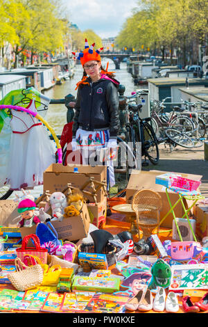 King's Day, Amsterdam, Netherlands. Girl selling toys and onther things on a bridge. Vrijmarkt' (flea market) in street Utrechtsestraat/Prinsengracht. - Stock Image
