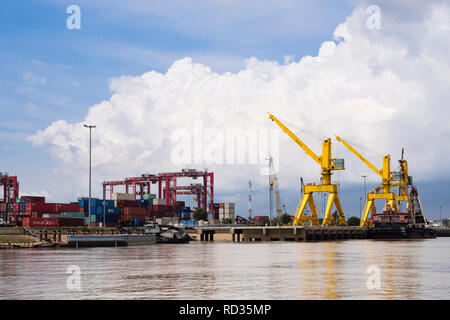 Cranes and gantries on riverside quay in container port seen from Mekong River. Kein Svay, Kandal province, Phnom Penh, Mekong Delta, Cambodia, Asia - Stock Image