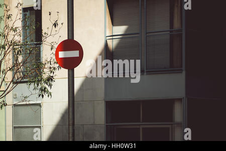 Red stop sign in Barcelona in front of facade of residential house with latticed windows and diagonal shadow, branches - Stock Image