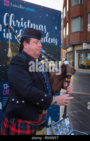 A lone piper busking in Leicester City Centre. - Stock Image