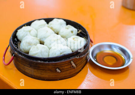 Traditional Chinese steamer basket with dim sum dumplings & chili oil, on a table in a Cantonese restaurant, - Stock Image