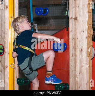Young Boy Striving To Climb a Climbing Wall Secured By A Safety Harness - Stock Image