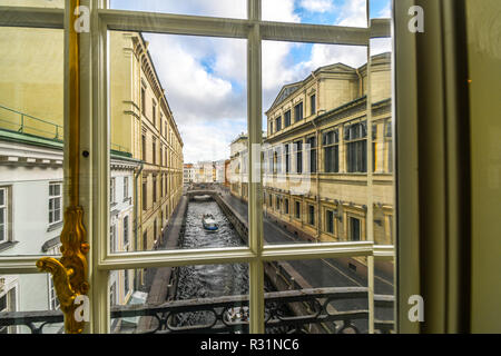 A tour boat glides down the Zimnyaya Kanavka Winter Canal and the Neva River in St. Petersburg Russia, view from a gallery window inside the Hermitage - Stock Image