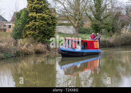 Group of people aboard the narrowboat 'Barney' on the canal at Cosgrove, Northamptonshire, UK; this boat is made available for day hire. - Stock Image