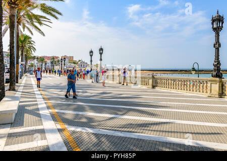 Tourists on the esplanade, Playa de La Caleta, Cadiz Spain - Stock Image
