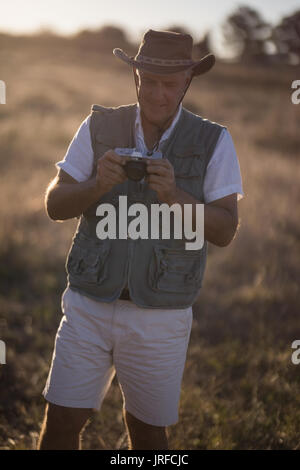 Man reviewing picture on camera during safari vacation - Stock Image