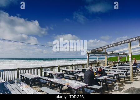 People relaxing on the outside decking area of the Fistral Beach bar in Newquay in Cornwall. - Stock Image