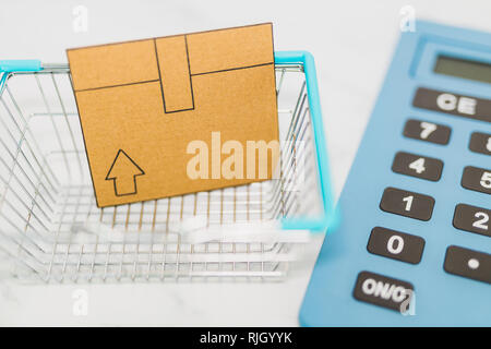 mini cardboard delivery parcel box into shopping basket and huge calculator in the background, concept of online shopping budget - Stock Image