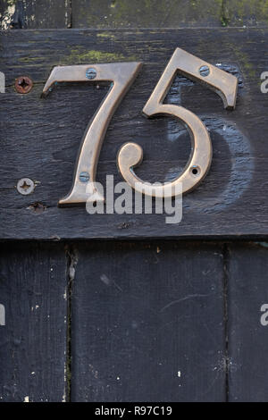 The number 75 on a gate. - Stock Image