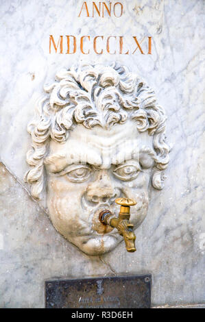 Roman-style Sculpted Head as an Outdoor Public Water Tap in a piazza in Aulla, Tuscany, Italy. - Stock Image