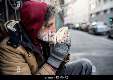A homeless beggar man outdoors in city, holding and smelling hot-dog. - Stock Image