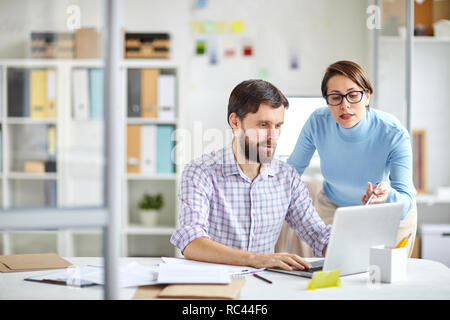 Confident office manager pointing at laptop display while explaining colleague online data or making presentation - Stock Image