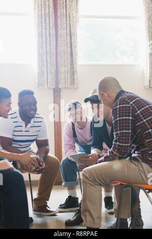 Men with digital tablet talking in group therapy circle - Stock Image