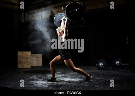 Side view of young woman weightlifting barbell in dark gym - Stock Image