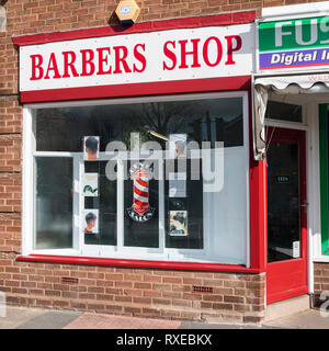 English village life - a mens' barber shop with photos on display and traditional red and white logo. - Stock Image