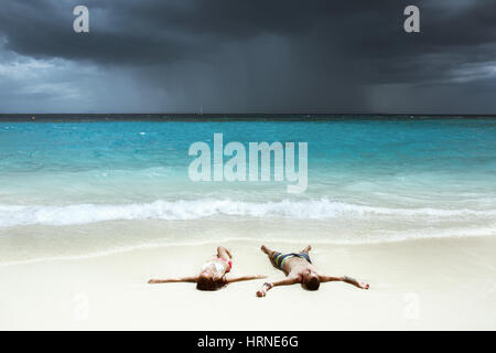 Idyllic photo of happy couple relaxing on white beach and tranquil sea backdrop. Space for text - Stock Image