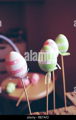 A beautiful close-up of 3 easter eggs on sticks over tables with an amazing depth of field as background - Stock Image