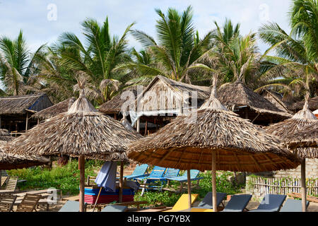 Detail of straw umbrellas and teepee-style house roofs in An Bang beach, in Central Vietnam. The coastal town is situated near the UNESCO protected to - Stock Image