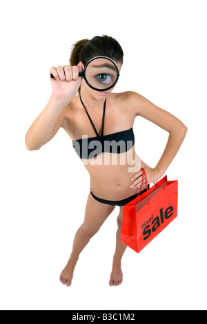 Young attractive girl in a sexy bikini magnifying her big blue eye and holding a final sale red shopping bag - Stock Image