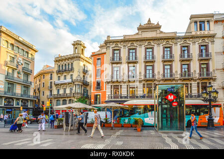 Pedestrians walk the colorful street La Rambla past buses and shops in Barcelona Spain - Stock Image