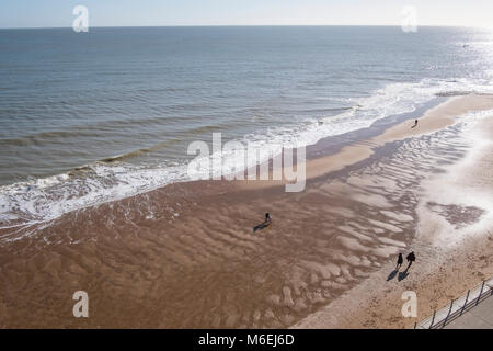 People walk on the sandy beach at Ramsgate as the tide recedes. - Stock Image