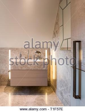 Washbasin and mirror in tiled bathroom - Stock Image