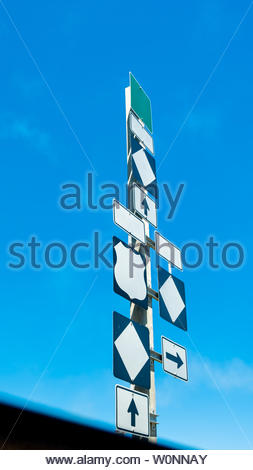 Three highway direction signs with arrows pointing up and right, three blank diamonds, one blank shield, one blank square, three blank rectangles. - Stock Image