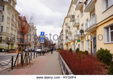 Poznan, Poland - March 8, 2019: Shrub and barrier along apartment building and road on the Slowackiego street. - Stock Image